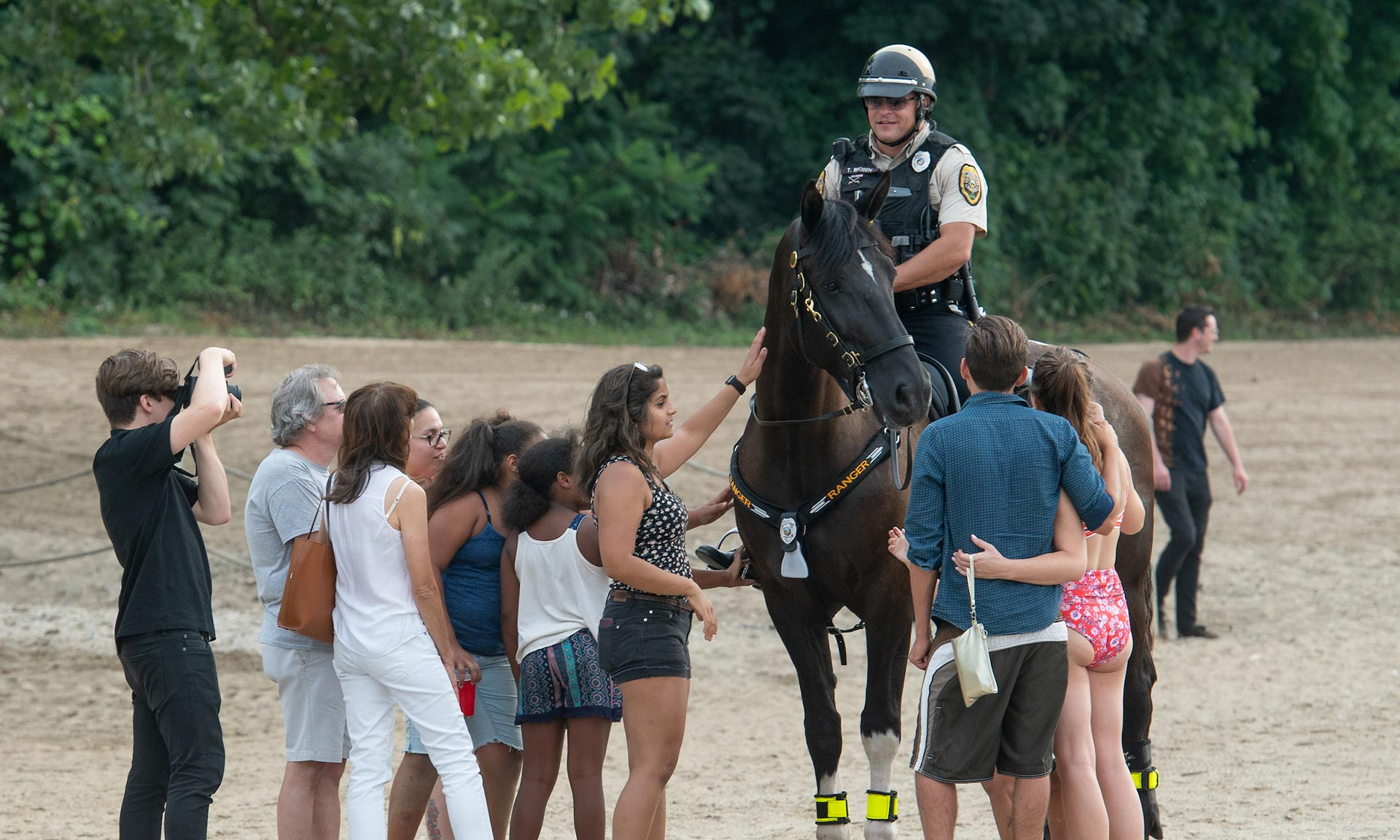 Mounted Ranger on the beach with a crowd